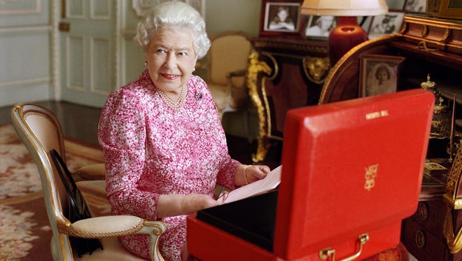 Queen Elizabeth II at her desk in her private audience room at Buckingham Palace with one of her official daily red  boxes containing important papers from government ministers. The photo was taken by Mary McCartney in July 2015, to mark the moment she becomes the longest reigning British monarch, with more than 63 years on the throne.