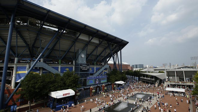 FILE - In this Aug. 27, 2018, file photo, fans walk outside of Arthur Ashe Stadium during the first round of the U.S. Open tennis tournament in New York. Governor Andrew Cuomo announced, Tuesday, June 16, that the U.S. Open will be played in Queens from Aug. 31 to Sept. 13, but without fans in attendance.
