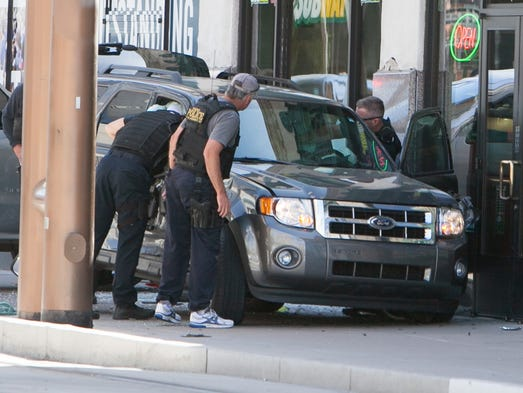 Phoenix police officers on the scene of a shooting on Jefferson Street, between First Avenue and Central Avenue, in downtown Phoenix on March 18, 2014.