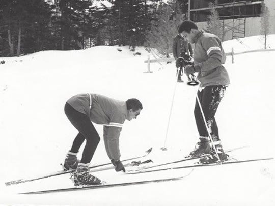 Instructor Bob Gratton helps Muhammad Ali learn to ski a Mount Snow beginner's trail in 1970.