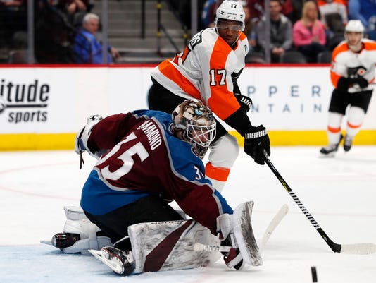Colorado Avalanche goaltender Andrew Hammond, front, deflects a shot by Philadelphia Flyers right wing Wayne Simmonds during the second period of an NHL hockey game Wednesday, March 28, 2018, in Denver. (AP Photo/David Zalubowski)