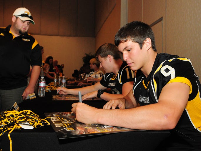 Southern Miss quarterback Nick Mullens, right, signs autographs for fans during the 19th annual Eagle Fanfare at the Lake Terrace Convention Center.