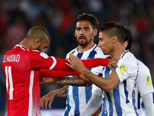 Morocco's Wydad Athletic Club Ismail El Haddad, left, discusses with Mexico's Pachuca Jonathan Urretaviscaya, right, and Franco Jara during the Club World Cup soccer match between Pachuca and Wydad Athletic Club at Zayed sport city in Abu Dhabi, United Arab Emirates, Saturday, Dec. 9, 2017. (AP Photo/Hassan Ammar)