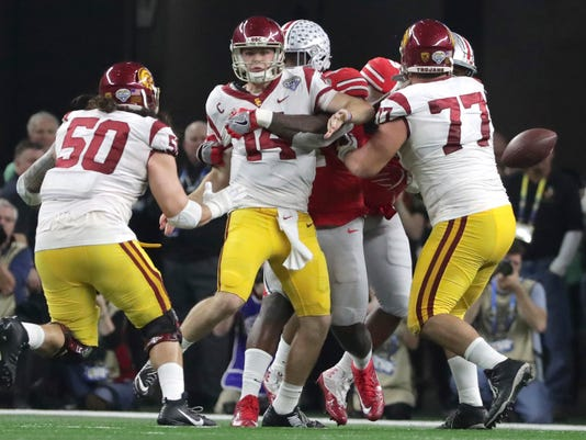Ohio State defensive end Jalyn Holmes, center, hits Southern California quarterback Sam Darnold (14) ,forcing a fumble during the fourth quarter of the Cotton Bowl NCAA college football game in Arlington, Texas, Friday, Dec. 29, 2017. Also in the play are Southern California guards Toa Lobendahn (50) and Chris Brown (77). Ohio State, which recovered the fumble, won 24-7. (AP Photo/LM Otero)