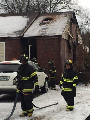 Fire fighter gather their gear after battling a blaze on Warfield Dr.