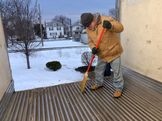 As an odd job to earn some money Millville resident Scott Lacey, who is homeless, cleans out the inside of a cargo trailer there, Tuesday, Jan. 26.
