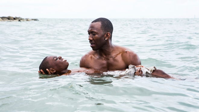 "This image released by A24 shows Alex Hibbert, foreground, and Mahershala Ali in a scene from the film, ""Moonlight.""  (David Bornfriend/A24 via AP)"