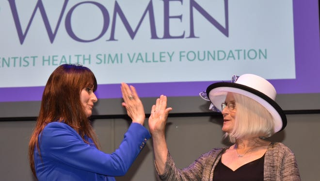 Inspirational speaker Kate Adamson, left, uses her one good hand to clap with Kathy Weiner at the Hats Off To Women event Friday.