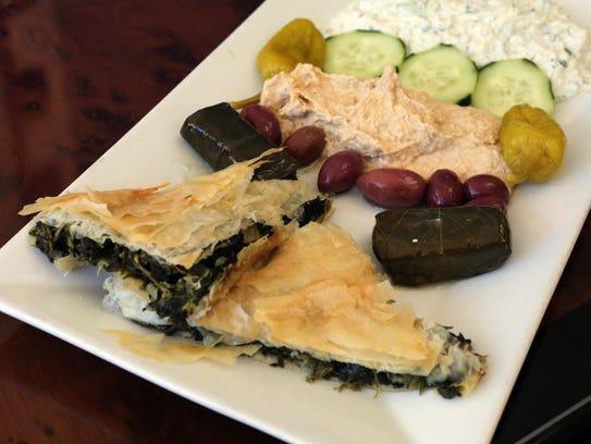 An appetizer selection including spinach pie, dolmadakia,