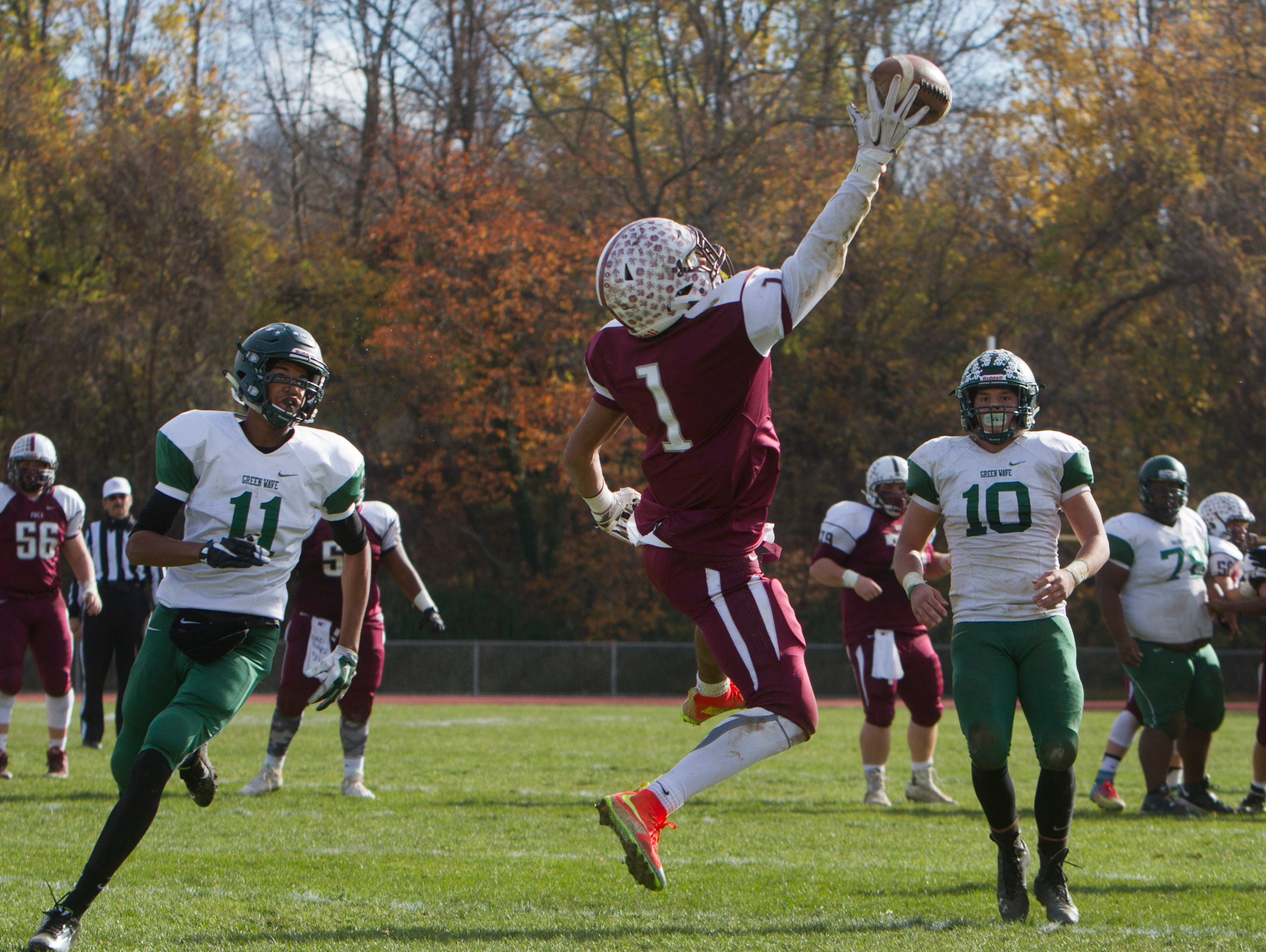 Red Bank Regional's Teddy Mitchell pulls down a pass over the middle and heads into endzone for his team's third touchdown of game. Long Branch vs Red Bank Regional Thanksgiving Day Football game in Red Bank NJ on November 26, 2015.