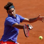 Roger Federer of Switzerland plays a shot to Alejandro Falla of Colombia during their men's singles match at the French Open tennis tournament at the Roland Garros stadium in Paris, France, May 24.