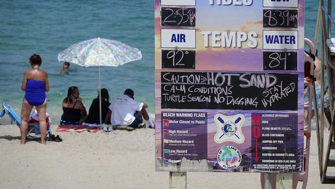 A sign cautions beachgoers about hot sand and encourages them to stay hydrated on a hot Tuesday afternoon,  in Lake Worth Beach.