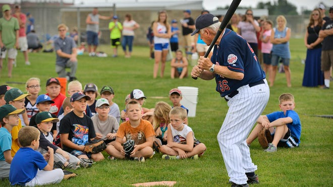 Young players and parents gather to watch as Ken Mauer Sr., uncle of Twins star Joe Mauer, teaches them how to hold and swing a bat during the Minnesota Twins Play Ball! Youth Baseball Clinic on Friday at Foley High School.