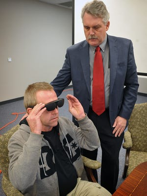 Andy Millard, a legally blind client of Beacon Lighthouse, tries on a NuEyes device which helps the visually impaired to see, read, write and more. Phillip Monroe, a representative for TxEyeTech, demonstrated the head-worn technology Friday. Each pair costs about $6,000 and Beacon Lighthouse is hoping to raise $200,000 to help people who would benefit defray the cost of the glasses.