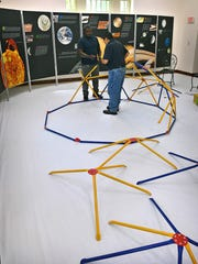 Delma Foster, left, and Pete Martinez assemble the framework of a space dome reading area in the Youth ArtZeum Outer Space exhibit at the Kemp Center for the Arts. The free exhibit has 9 different interactive stations for kids and adults to learn more about space.