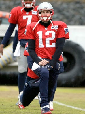 Patriots QB Tom Brady (12) stretches at practice this week.