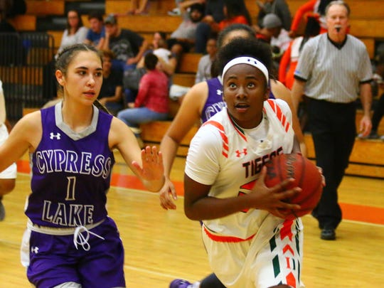 Dunbar freshman Luxury Vance drives to the basket past Cypress Lake's Star Cuevas in Dunbar's 76-8 home win Thursday, Dec. 7, 2017.