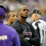 Minnesota Vikings running back Adrian Peterson stands on the sidelines during the first half of an NFL football game in 2013 against the Detroit Lions in Minneapolis.