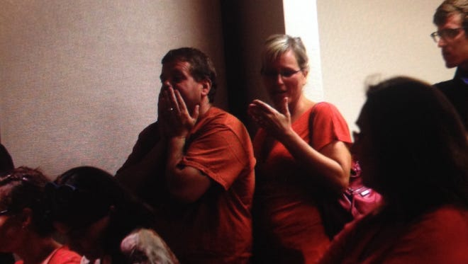 Robert and Pamela Burroughs react as the opt out vote is rescinded during a meeting at the Lee County School Board.