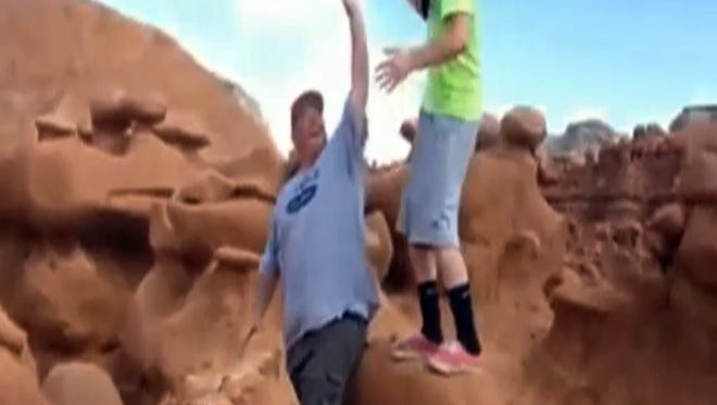 A frame grab from a video taken by Dave Hall shows Glenn Taylor and one of their friends cheering after Taylor, a Boy Scouts leader, knocked over an ancient Utah desert rock formation at Goblin Valley State Park on Oct. 11, 2013.