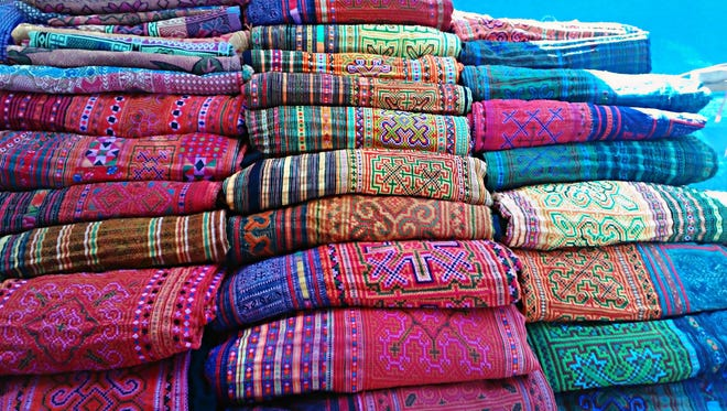 "Colorful Hmong fabrics for sale at a market in Chiang Mai, Thailand. Door County Reads is holding an exhibit and demonstration of Hmong textile art Feb. 7 at the Door County Library in conjunction with the county's exploration of the Kao Kalia Yang book ""The Latehomecomer: A Hmong Family Memoir."""