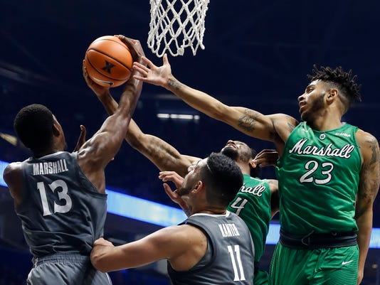 Xavier's Naji Marshall (13) and Marshall's Rondale Watson (23) battle for a rebound in the first half of an NCAA college basketball game, Tuesday, Dec. 19, 2017, in Cincinnati. (AP Photo/John Minchillo)