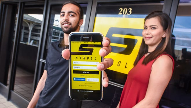 Amit Sachdev, left, Stroll Guam CEO and founder, displays the Stroll mobile application he had created, as he is photographed with administrative assistant Lisa Munoz in Tamuning on Thursday, Nov. 10, 2016. Sachdev developed the mobile app to connect people who need transportation with those with vehicles, willing to pick up and drop off riders.