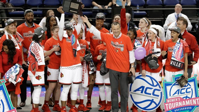Louisville players and coaches raise the trophy after their win over Notre Dame in an NCAA college basketball game in the championship of the women's Atlantic Coast Conference tournament in Greensboro, N.C., Sunday, March 4, 2018. (AP Photo/Chuck Burton)