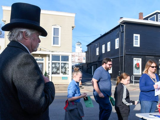 Dressed in period attire, complete with a top hat, John Strange watchers over a family buying roasted chestnuts at the Newburgh Celebrates Christmas event Sunday, December 3, 2017.