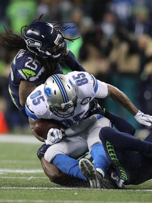 Eric Ebron makes a catch against Richard Sherman, top, during the second quarter Jan. 7, 2017 in a playoff game at Centurylink Field in Seattle.