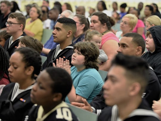 Seaman Recruit Carlos Lozada, left, from Chicago, and Landon Purdon, a fourth grade student at Myrtle Grove Elementary School, listen to the guest speakers during the Saturday Scholars graduation ceremony.