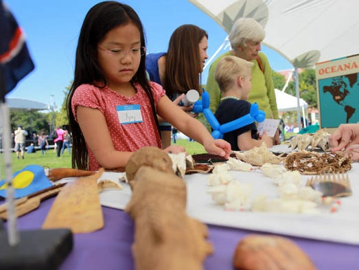 Yiying McGraw, 8, of Iowa City checks out a station in the children's area of the Cultural Diversity Festival at Hubbard Park on Sunday, Sept. 29, 2013.