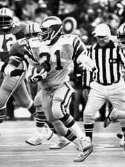 Eagles Wilbert Montgomery breaks away from Dallas Cowboys defenders to pick up more yardage in the NFC championship game in Philadelphia, Jan. 11, 1981.