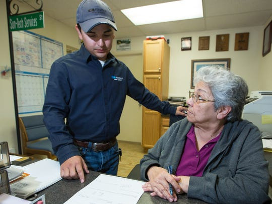 Sun Tech new owner Josh Corral, left, and office manager Margo Medina, Corral's grandmother, discuss business on Monday April 11, 2016 the offices located at 750 W. Las Cruces Ave.