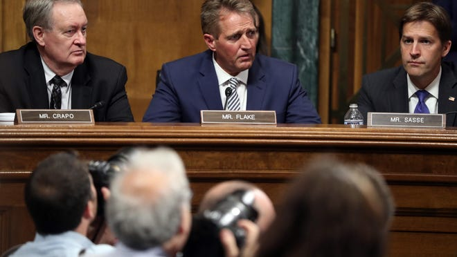 Sen. Jeff Flake, R-Ariz., speaks during the Senate Judiciary Committee meeting on Friday, Sept. 28, 2018, on Capitol Hill in Washington, as Sen. Mike Crapo, R-Idaho, left, and Sen. Ben Sasse, R-Neb., listen. Flake said it would be 'proper' to delay a Senate floor vote on Supreme Court nominee Brett Kavanaugh for a week. (AP Photo/Andrew Harnik)