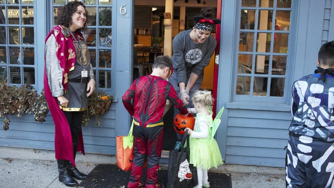 Amanda from Raw Bob's Organic Juicery on Broadway hands out candy to trick-or-treaters while Diana Wood from the East Bay Community Action Program leads the Broadway Halloween Stroll in 2018. It appears unlikely the event will happen this year due to coronavirus-related concerns.