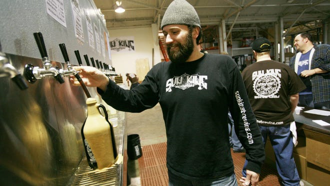 Sun King's Clay Robinson fills a growler of beer at its brewery on College Avenue. On Fridays, growler fills are $6.