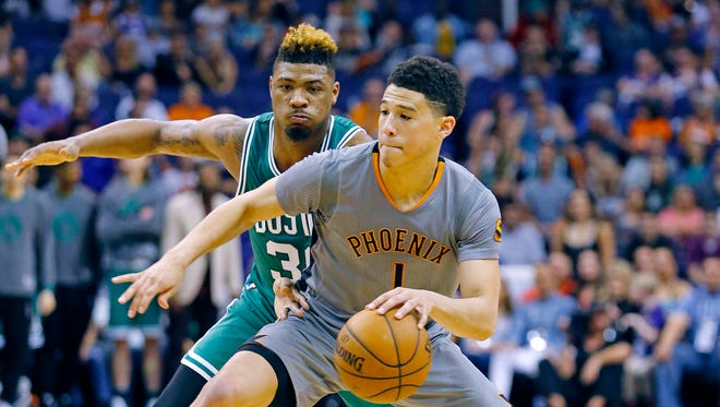 Phoenix Suns guard Devin Booker (1) works against Boston Celtics guard Marcus Smart (36) in the second half of their NBA game March 26, 2016 in Phoenix, Ariz.