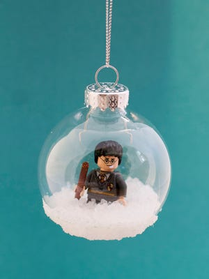 A Harry Potter Lego minifigure enclosed in a plastic Christmas tree ornament bulb. The bulb is cut open to insert the toy and glued back together. Epsom salt gives it a snowy look and cover up the cutting line.