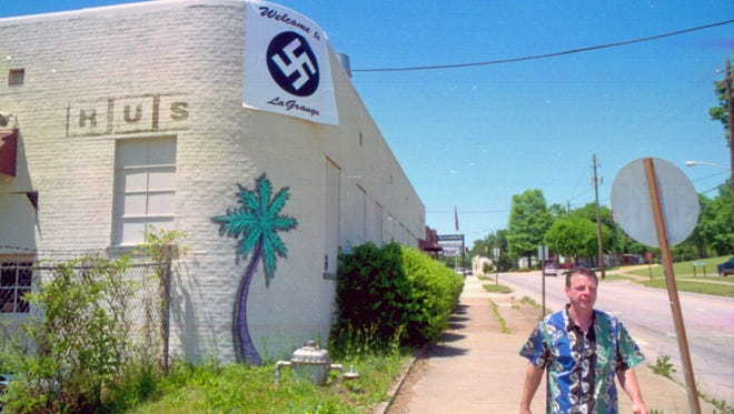 """This April 27, 2001 photo shows James """"Rusty"""" Houser walking down Main Street in LaGrange, Ga., next to his bar, Rusty's Buckhead Pub, displaying a banner to compare a LaGrange City Council decision to pull his alcohol license to Nazi tactics."""