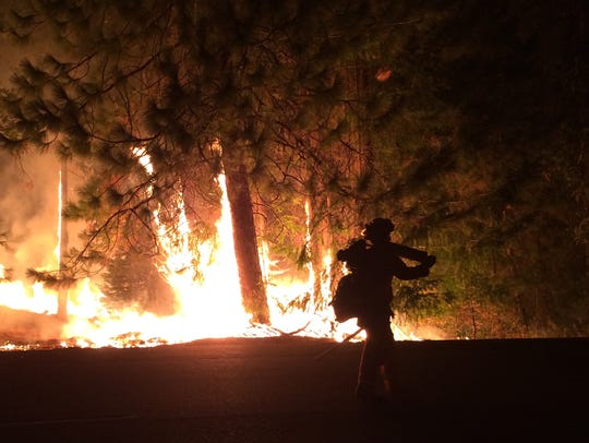 A firefighter walks past the King Fire on Highway 50