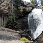 Hikers from Dallas, Texas, take a photo May 25, 2015, of Ouzel Falls, located in the Wild Basin area of Rocky Mountain National Park.