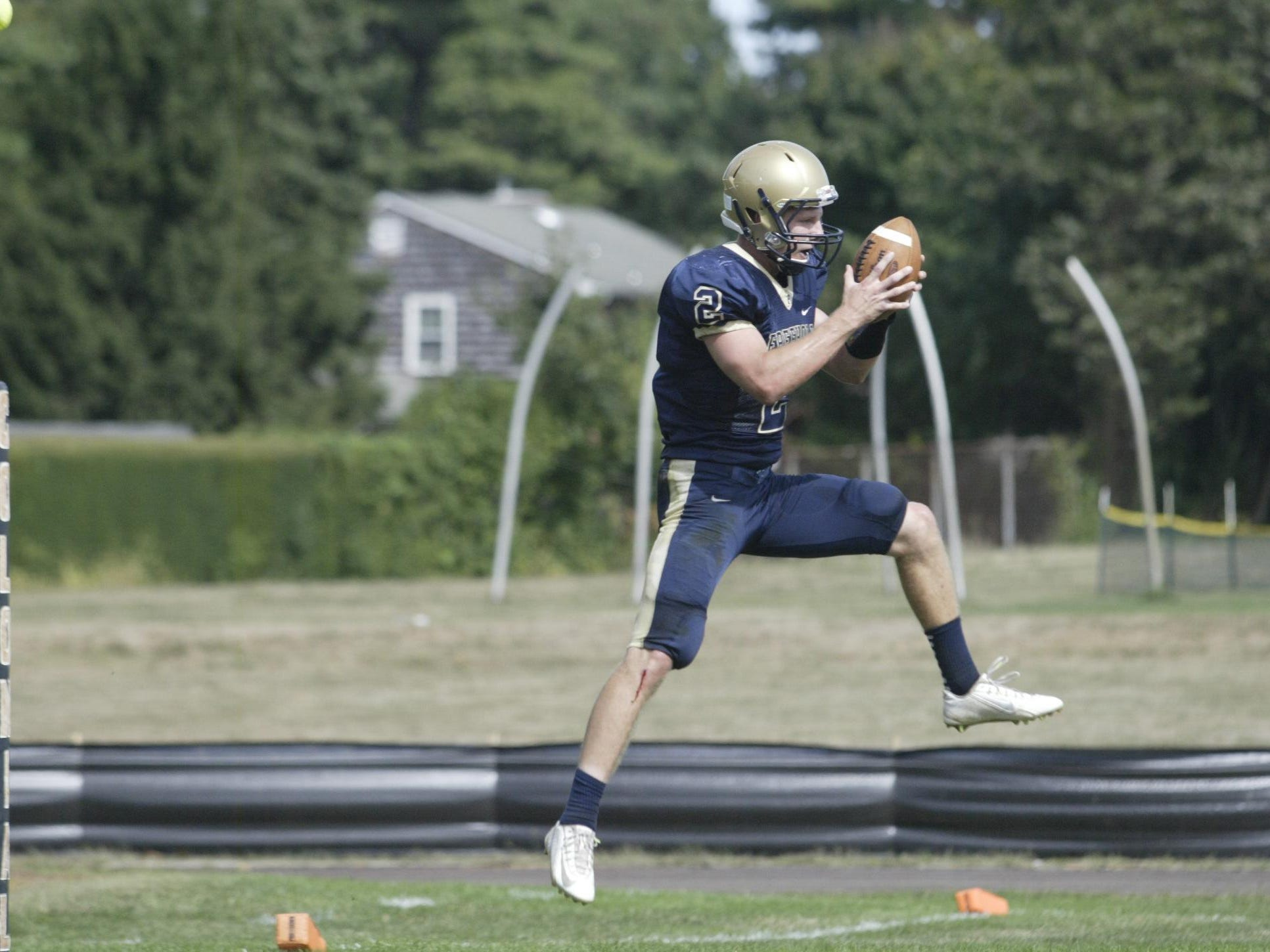Freehold High School punter Jake Curry leaps in the air to corral an errand toss from the center in a Shore Conference game against Middletown North High School, Saturday afternoon, at Freehold.