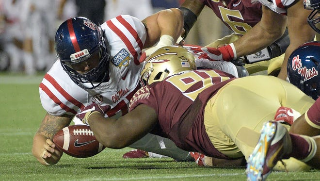 Florida State defensive tackle Derrick Nnadi, center, grabs an Ole Miss fumble during the second half Monday in Orlando.