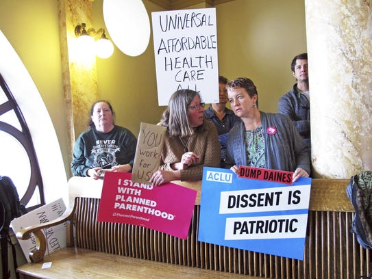 Protesters wait for U.S. Sen. Steve Daines to hold
