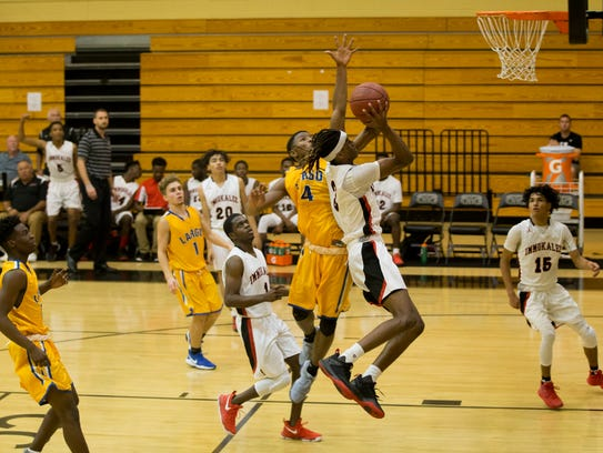 Immokalee's Hasahnn Reynolds (3) lays the ball up against