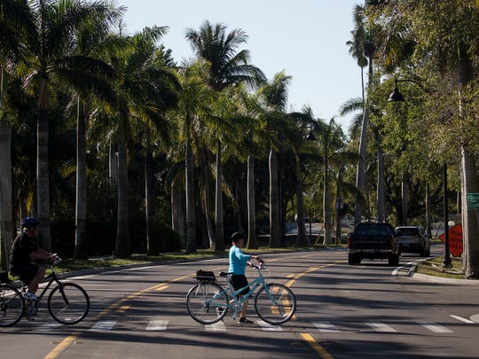 Cyclists cross McGregor Boulevard near the Fort Myers