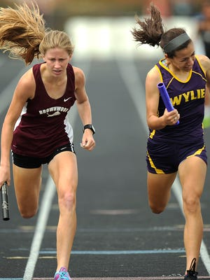 Wylie's Leandra Benton (right) lunges over the line ahead of Brownwood's Kyra Young to win the girls 1600m relay during the District 5-4A track meet on Thursday, April 13, 2017, at Wylie's Bulldog Stadium. Wylie won the race by .01 seconds.