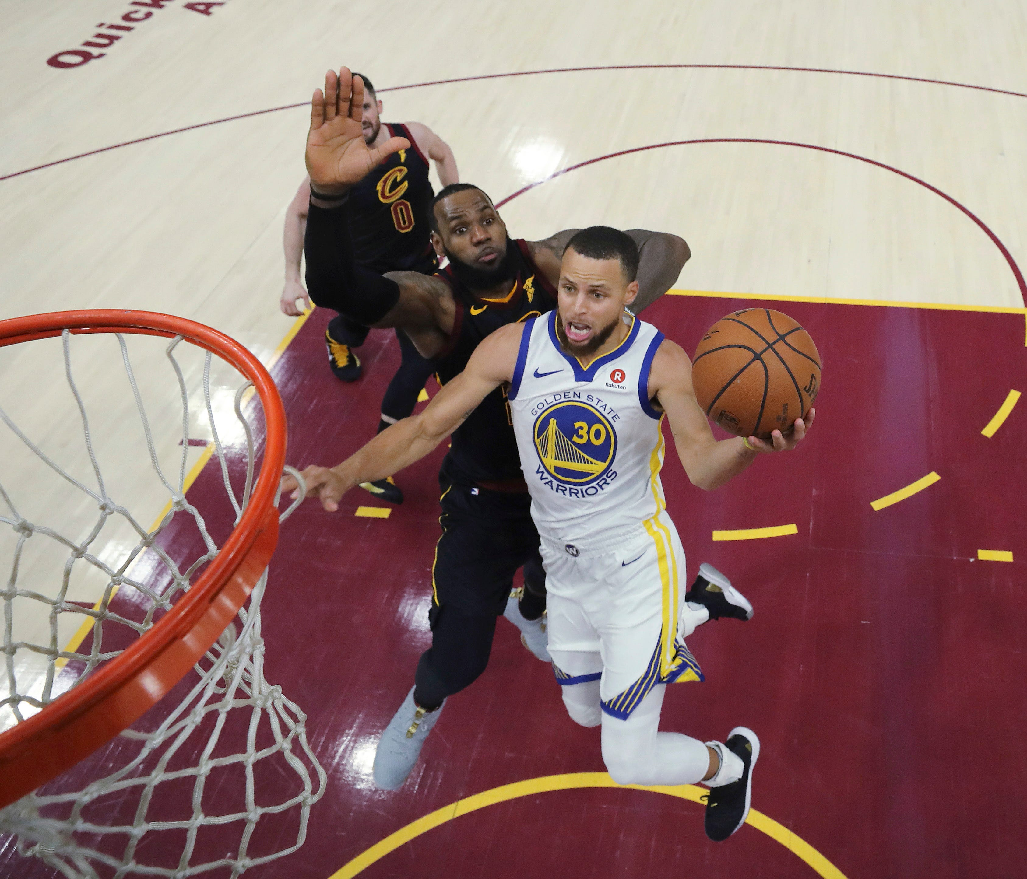 Golden State Warriors' Stephen Curry shoots next to Cleveland Cavaliers' LeBron James during the second half of Game 3 of basketball's NBA Finals, Wednesday, June 6, 2018, in Cleveland. The Warriors defeated the Cavaliers 110-102 to take a 3-0 lead i