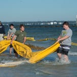 """Catholic High School students and volunteers work on a shoreline restoration project at Deadman's Island in Gulf Breeze. The """"Make a Difference Day"""" activity is designed to help stabilize the island's fragile shoreline."""
